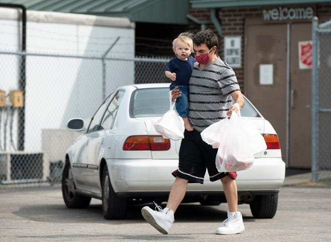 Kenny Pieper and his son, Aries, 1, head back to their vehicle with lunches at the Salvation Army, 1040 N. Fulton Avenue, Tuesday morning, Sept. 15, 2020. The facility offers free meals Monday through Friday from 11 a.m. until 1 p.m. and served about 300 meals Tuesday.