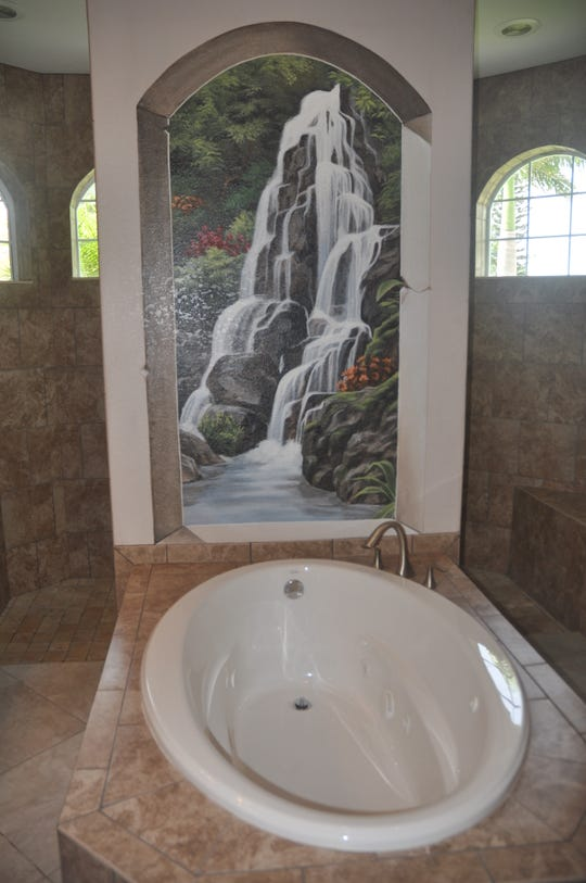The master bath of the three bedroom plus den and three bathroom home has a soaking tub with a waterfall mural.
