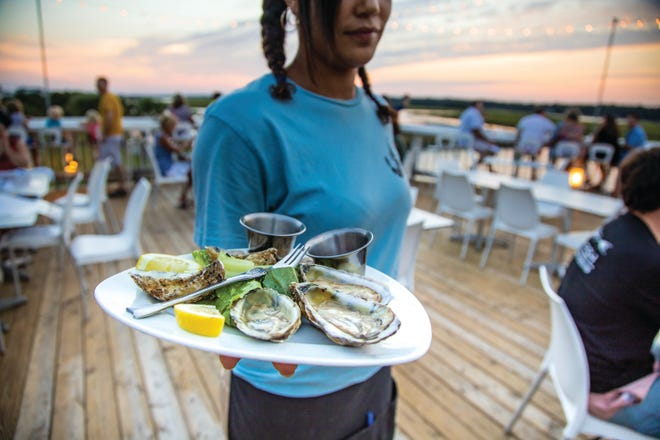 A server at Jinks Creek Waterfront Grille in Ocean Isle Beach holds a plate of oysters.