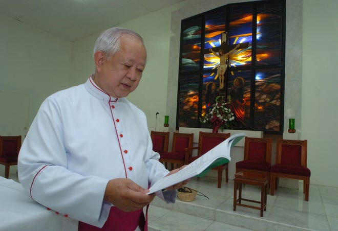 In this 2007 file photo, Monsignor David I.A. Quitugua holds a CHamoru lectionary translated by Bishop Tomas A. Camacho of Saipan at the San Juan Bautista Church in Ordot. Quitugua died Tuesday from COVID-19.