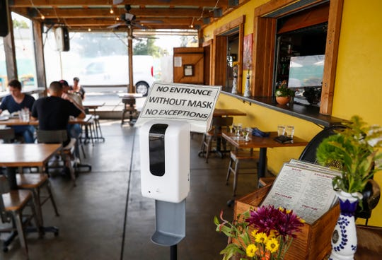 Customers sit in an enclosed seating area and are required to wear a mask upon entering the restaurant at Festiva off of East 16th Street in Indianapolis, Saturday, Sept. 12, 2020. Restaurants had to adapt to the takeout business during the pandemic.