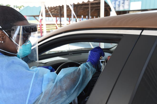 UAMS registered medical assistant Natasha Cleveland performs a COVID-19 test Tuesday on a driver at the Baxter County Fairgrounds during a free testing event. The testing was so popular, officials ran out of test kits.