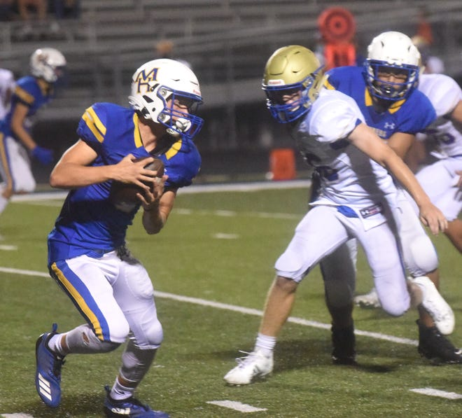 Mountain Home's Masen Walker carries against Harrison on Monday night.