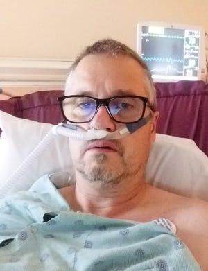 Blackford athletic director Tony Uggen sits in a hospital bed at IU Health Ball Memorial Hospital.
