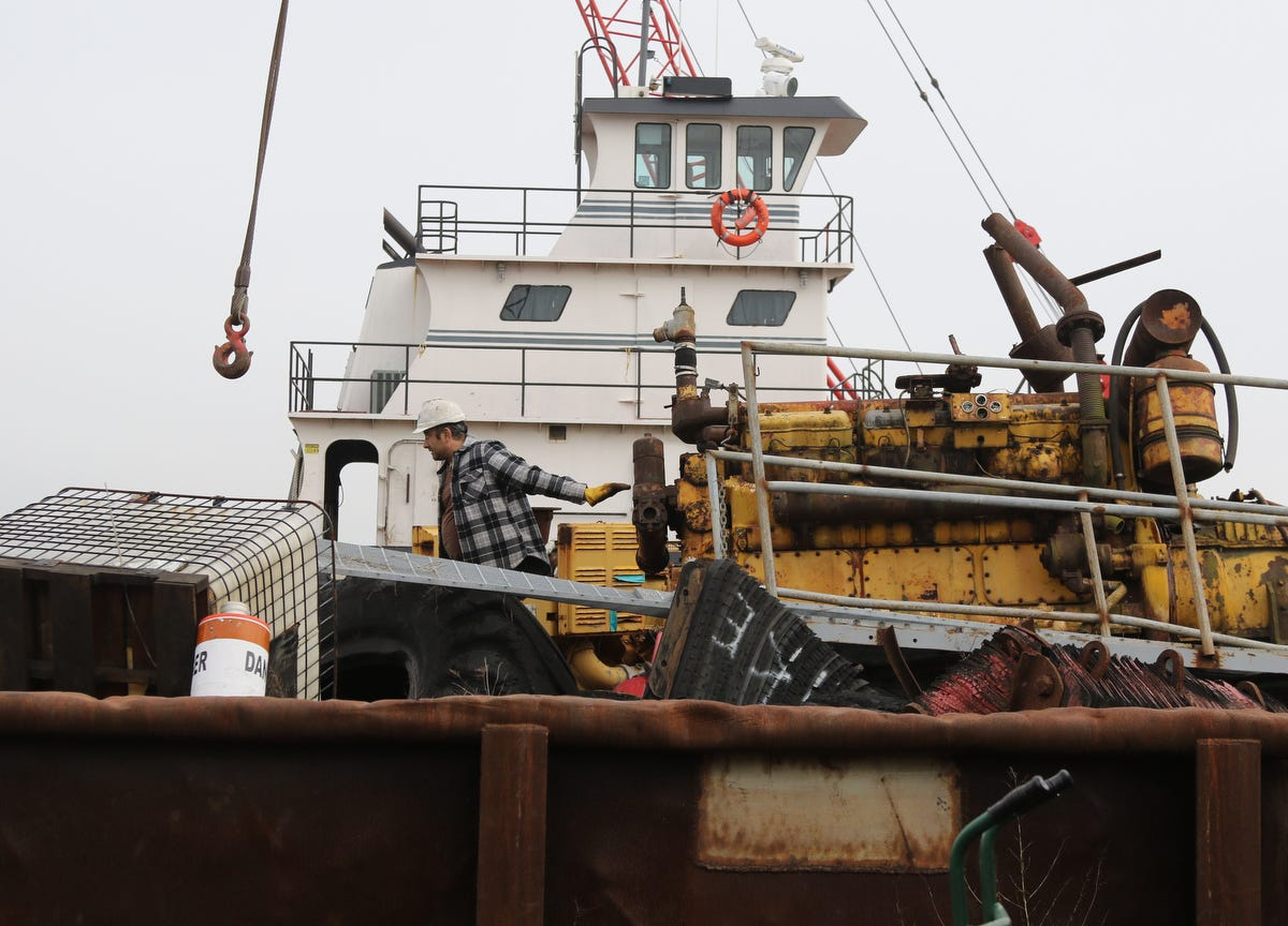 """Mike Vinik navigates heavy equipment moored on barges alongside his tugboats at """"Vinik Island,"""" his agglomeration of marine equipment in The Kills."""