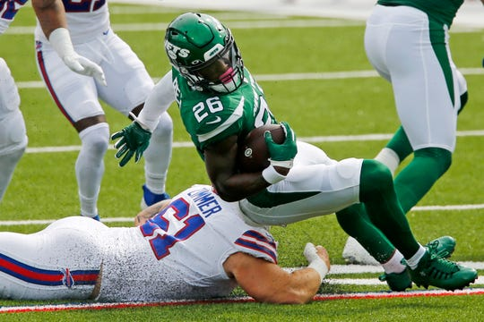 New York Jets running back Le'Veon Bell (26) is brought down by Buffalo Bills' Justin Zimmer (61) during the first half of an NFL football game in Orchard Park, N.Y., Sunday, Sept. 13, 2020.