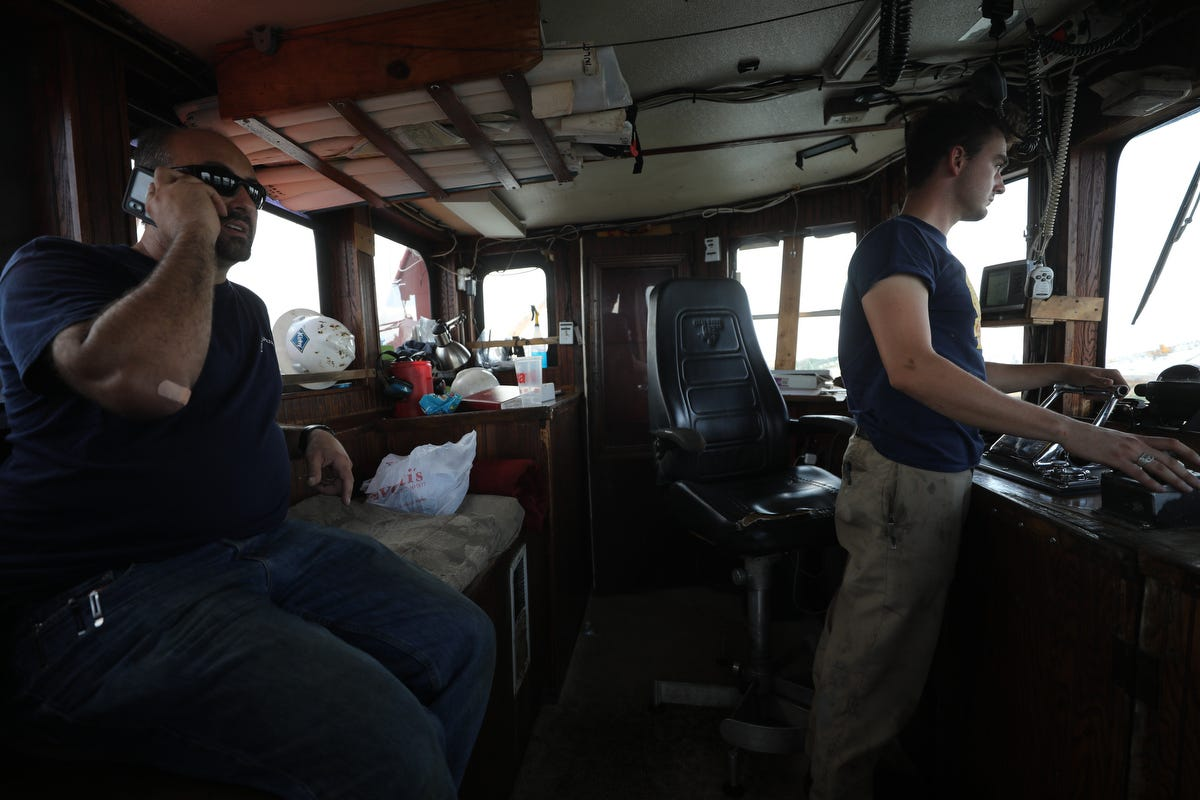 Mike Vinik and Corey, a deckhand, in the pilot house of a Vinik Marine tug.