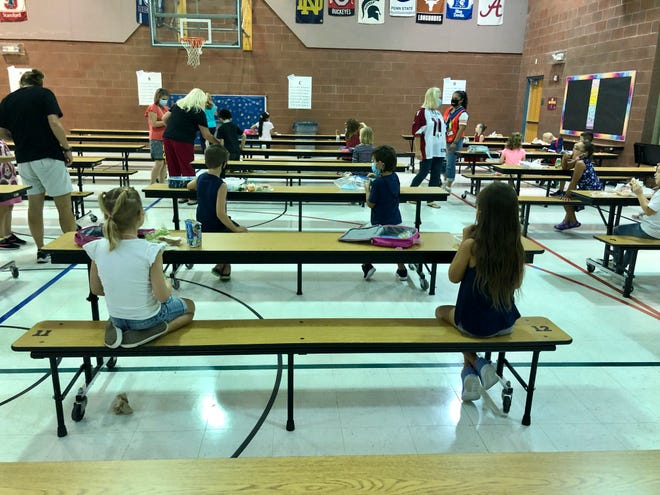 At Conley Elementary School in Chandler, students eat lunch one grade level at a time, two students to a table, all facing the same direction.
