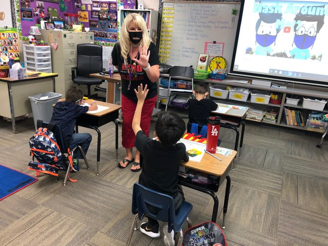 Carrie Collins, a first-grade teacher at Conley Elementary School in Chandler, shows a student how to do an air high-five, same as a regular high-five except they did it at a distance and didn't touch hands.