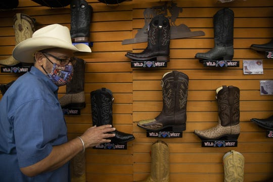 Miguel Pena, co-owner of Botas Juarez, explains the detail on a pair of Wild West cowboy boots, in Phoenix on Sept. 11, 2020.