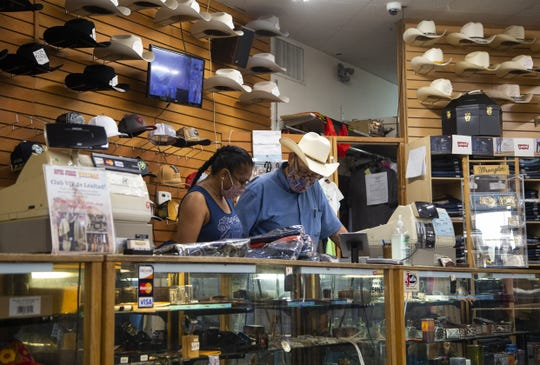 Miguel Pena, co-owner of Botas Juarez, talks to an employee. in Phoenix on Sept. 11, 2020.