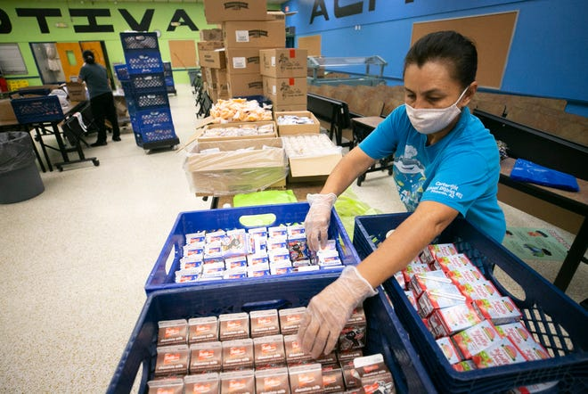 Consuelo Delgado, a cook with Peralta Elementary School, prepares a breakfast and lunch combination meal for a free food distribution at Peralta Elementary School in Phoenix on Sept. 14, 2020.