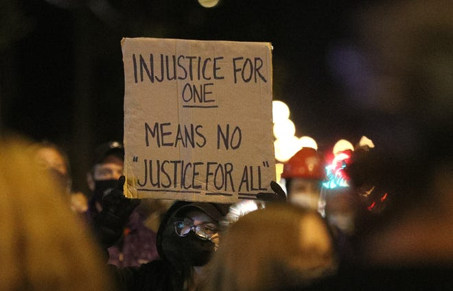 A protester holds a sign as a group gathers on Jefferson Ave.