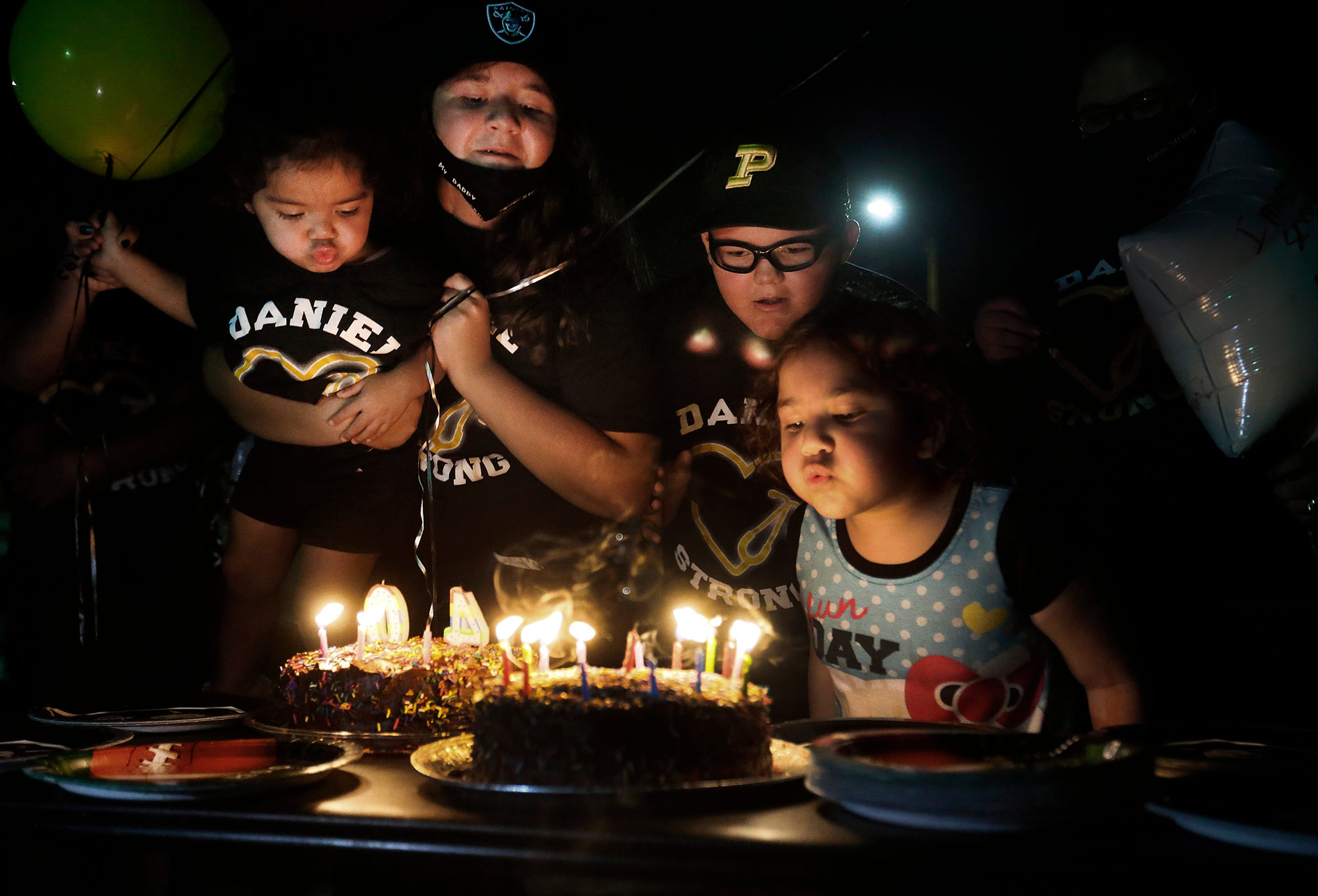 Desiree, from left, Danika, Dominik and Daniella Morales blow candles out to honor their late father Daniel Morales on what would have been his 40th birthday Aug. 21, 2020.