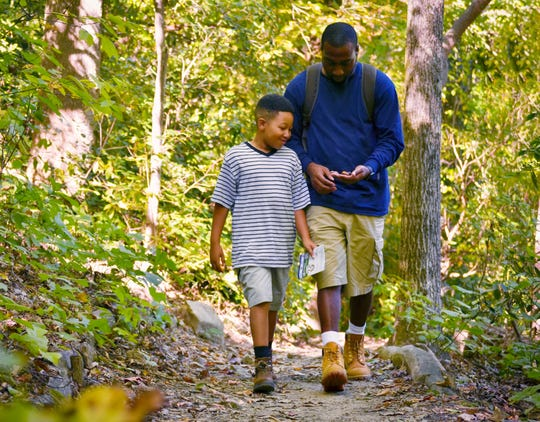 A father and son walk down a trail.