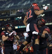 San Diego State running back Chase Jasmin is hoisted by offensive lineman William Dunkle during last season's game against Fresno State at SDCCU Stadium.