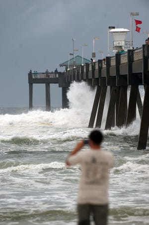 The waves crashed onto the fishing pier on the island of Ocalusa on Monday evening as winds and waves from Hurricane Sally began to hit the Emerald Coast.