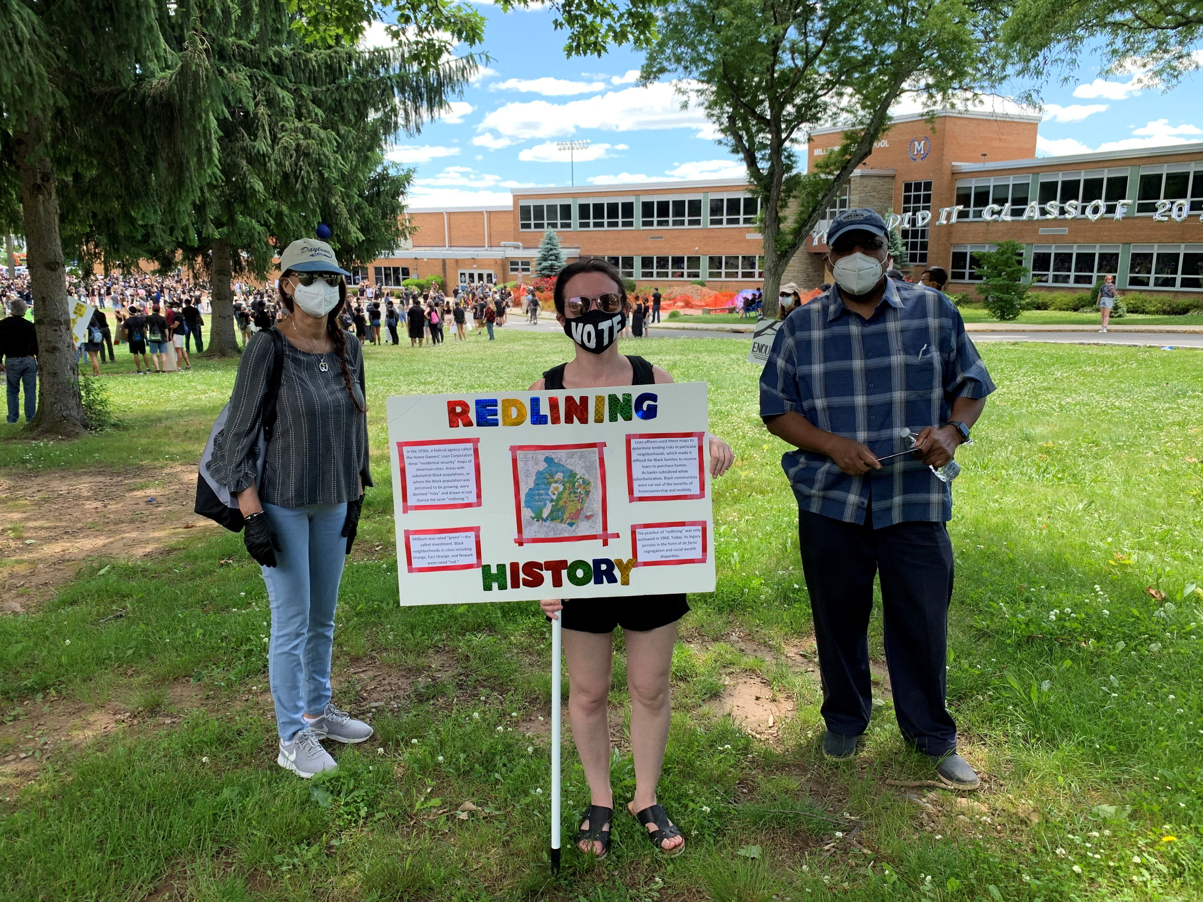 Courtney Cooperman attended a Black Lives Matter rally in Millburn, N.J., in June with a poster showing a history of redlining in Essex County.