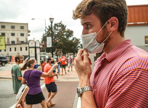 Ryan Coffey, right, a senior at Clemson University watches others visit downtown Clemson, S.C. Saturday, September 12, 2020.