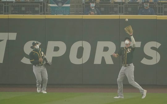 A's right fielder Stephen Piscotty wears a mask as he catches a fly ball hit by the Mariners' Kyle Seager as center fielder Ramon Laureano looks on as smoke from wildfires fills the air at T-Mobile Park.