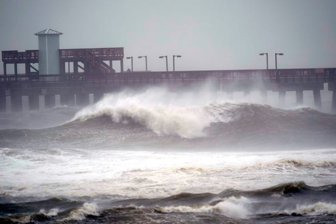 The waves crashed near a pier on Tuesday in Bay National Park in Gulf Shores, Alabama, before Hurricane Sally hit the North Bay Coast.