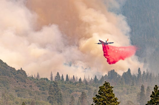 A tanker drops retardant as smoke from the SQF Complex Fire billows Monday, September 14, 2020, east of Springville.