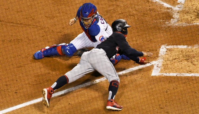 Chicago Cubs catcher Victor Caratini, left, tags out Cleveland Indians Francisco Lindor, right, at home plate during the third inning of a baseball game, Tuesday, Sept.15, 2020, in Chicago. (AP Photo/David Banks)