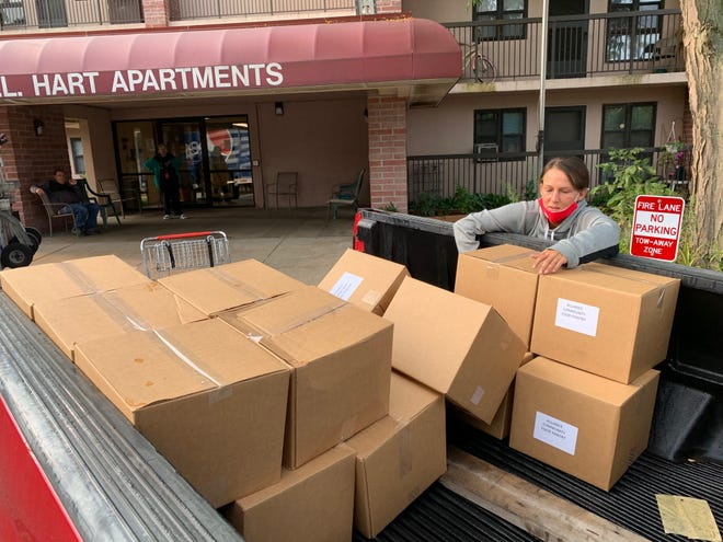 DoorDash driver Jen Greeneiser unloads food a the W.L. Hart Apartments Tuesday morning that she had picked up at the Alliance Community Pantry.