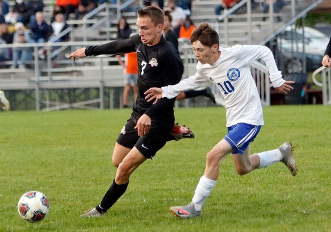 Ashland High's Dylan Kruty (7) and West Holmes' Brevin Bucher (10) fight for possession during high school boys soccer action on Tuesday at Ashland Community Soccer Stadium. The Arrows won, 10-0.