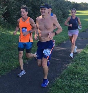 Peter Lederer, center, and Joe Haughey, left, get support from Allyson Thompson, right, during Saturday's Boston Virtual Marathon in and around Tyler State Park.