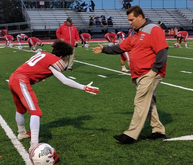 Freedom athletic director John Rosa shakes hands with a Bulldog player during a game in 2018 when he was interim football coach.
