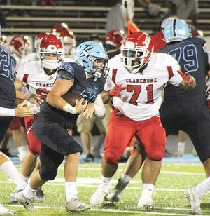 Sam Phillips, center, bursts through tight space to gain some yards for Bartlesville High School during varsity football action earlier this month.