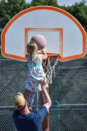 A little girl gets a lift from her dad to help her make the shot at Memorial Park in Barnesville recently.