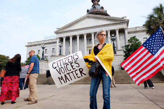 Kim Rulf of Greenville attends a protest on the South Carolina Statehouse grounds in Columbia on Tuesday calling for Gov. Henry McMaster to end the state of emergency issued for the coronavirus pandemic and for lawmakers to remove mask mandates across the state.