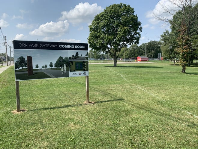 """The white line to the right of the """"Coming Soon"""" sign shows where the new pathway will cut through the grassy lot on West High Street. The walkway will start at the corner of Ella Street and end at Schmid Hall on Hall Street."""