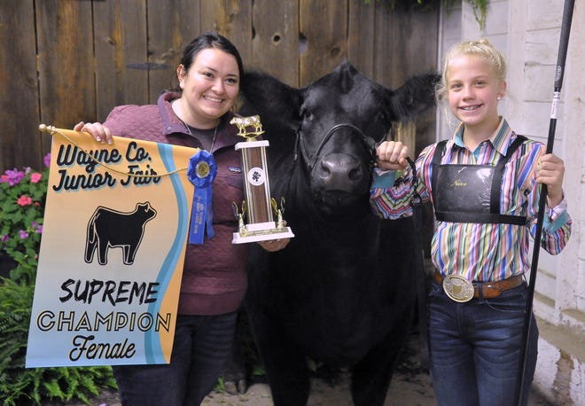Delaney Dudte, right won the supreme female, pro showmanship and junior showmanship in the beef breeding show,  Brooke Hayhurst, left, holds her awards.