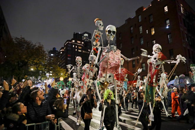 FILE - Revelers march during the Greenwich Village Halloween Parade in New York on Oct. 31, 2019. The holiday so many look forward to each year is going to look different in the pandemic as parents and the people who provide Halloween fun navigate a myriad of restrictions and safety concerns.