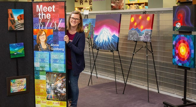 Annie Guldberg makes the final arrangement of her artwork on display at the Mount Pleasant Public Library.