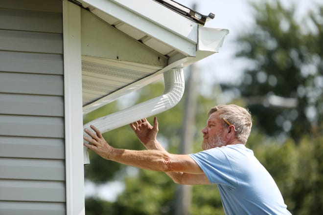 Jim Pearson, of Pearson's Seamless Gutter, attaches a downspout elbow while installing a new gutter Tuesday at a Burlington home.