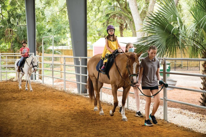 Volunteer Peyton Harvey (front) leads her sisters, Presley (center) and Parker in a therapeutic horse ride at the North Florida School of Special Education's newly opened equestrian center.