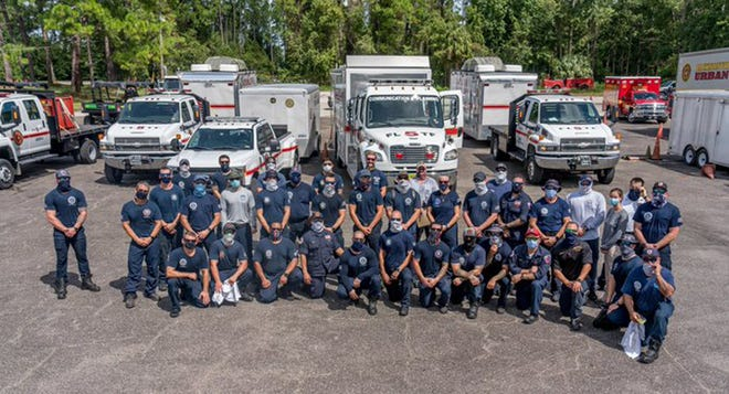 A team of 41 Jacksonville Fire and Rescue urban search and fast water teams take a group photo before they head to the Panhandle to help Hurrricane Sally.