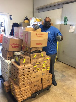 Zee, a BEAM warehouse worker, unloads essential grocery items for senior hurricane kits.