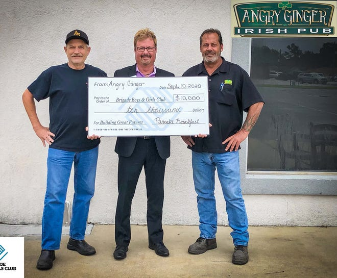 Angry Ginger restaurant owners Paul Myers and Shawn Curtis presented the Brigade Boys & Girls Club of Onslow County executive director Keith Williams with a $10,000 check. The restaurant raised funds for the club during a recent pancake breakfast fundraiser. [Contributed photo]