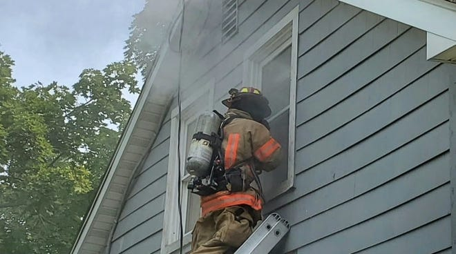 A firefighter stands on a ladder while the Stow Fire Department conducts a training session at a vacant North River Road home.