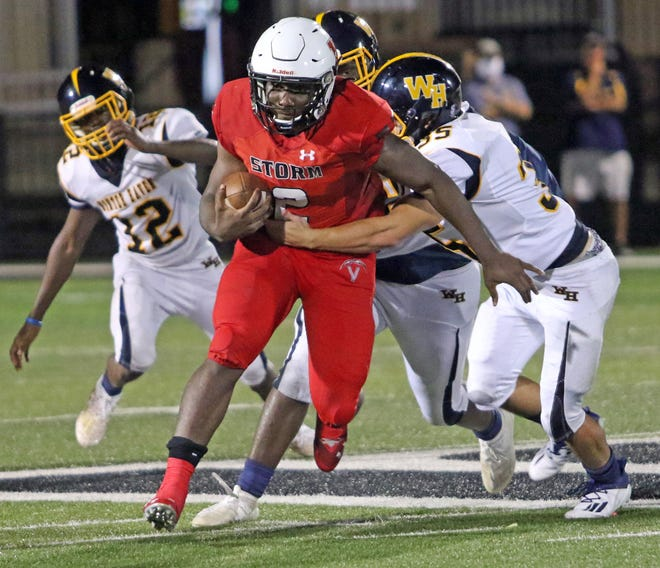 Victory Christian running back Cornelius Shaw looks for running room as Winter Haven linebacker Luke Deangelis tries to wrap him up. [ROY FUOCO/THE LEDGER]