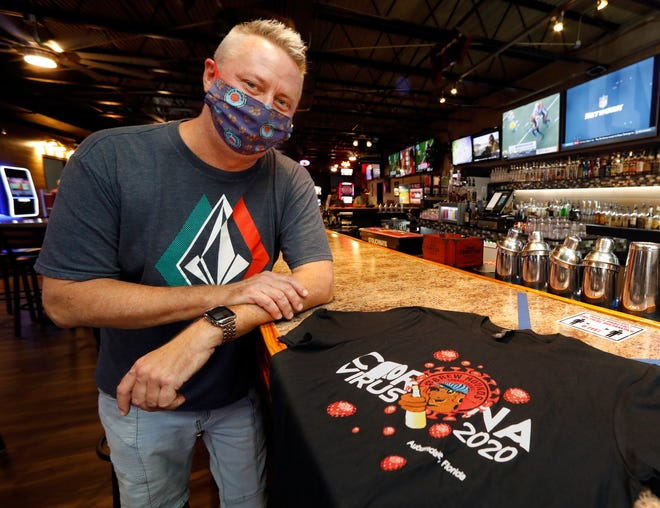 Skip Jacobs, co-owner of Brew Hounds Sports Lounge, has reopened the bar and displays a T-shirt being sold to help the staff in Auburndale.