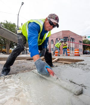 Construction worker Pedro Duran, from DAB Constructors Inc., uses a float to smooth out the freshly poured concrete in front of the Symmetry Coffee & Crepes eatery near downtown Ocala earlier this week.  Job growth in the local construction sector is strong, leading to an improved unemployment rate.