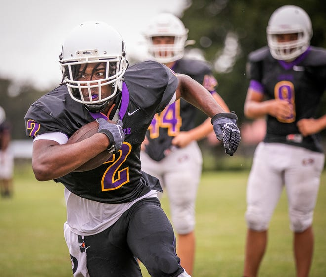Lake Weir running back Thamydious McClain carries the ball during a drill at football practice. The Hurricanes open up their season against the Dunnellon Tigers Friday night.