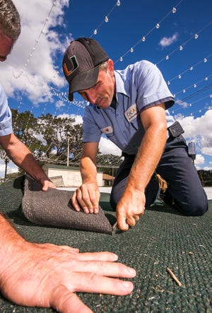 Jeff Mackey with the City of Ocala cuts a section of carpet in this  2017 file photo. On Tuesday, the Ocala City Council tentatively approved the 2020-21 city budget. The council will vote on the final approval of the budget on Sept. 22.