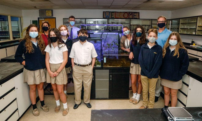 A group of Palm Beach Day Academy students and teachers inside the school's coral reef lab on Wednesday.  Teacher Jonathan Paine (back right) helped produced a 30-minute documentary about the lab that will air on PBS starting Saturday. DAMON HIGGINS/The Palm Beach Daily News